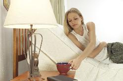 Picture of woman enjoying coffee in bed.